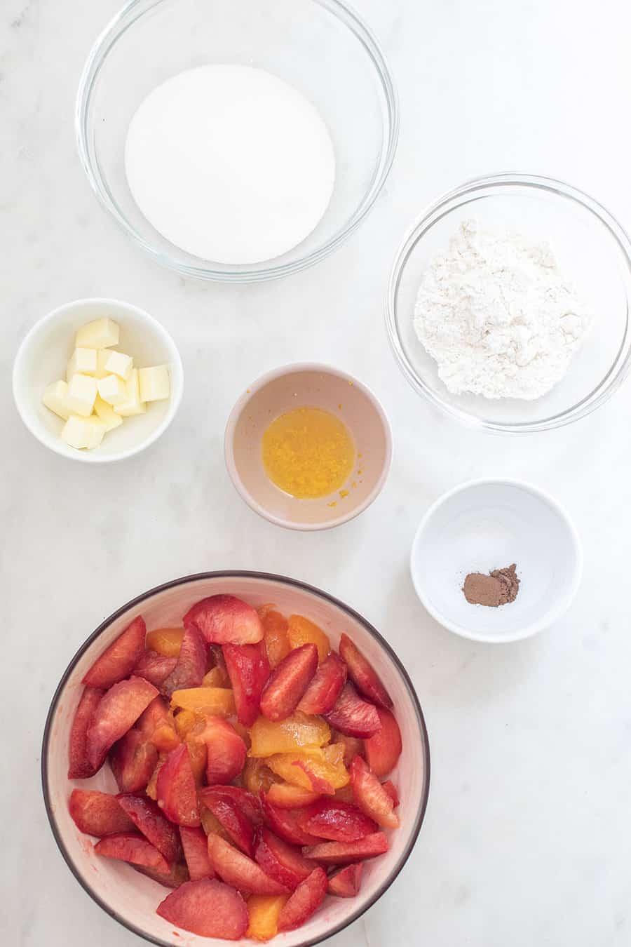 sugar, butter, orange, flour, slices and sliced fruit in a bowl.