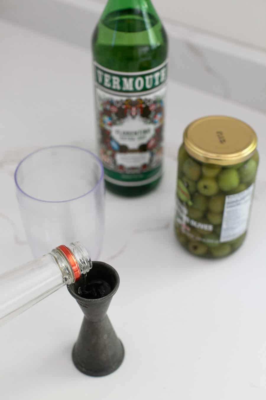 Pouring vodka into a jigger with olives in the back.
