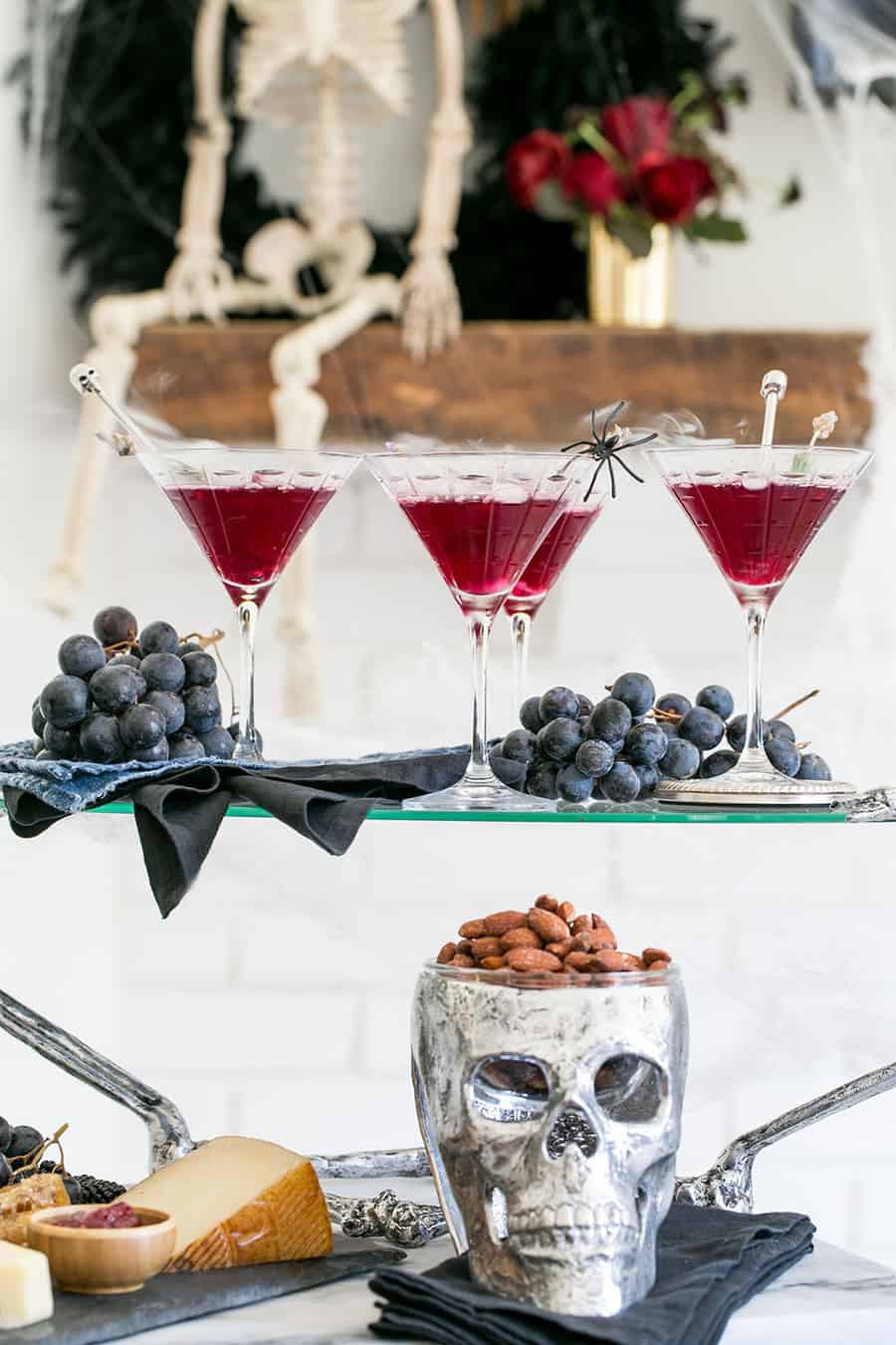 Halloween cocktails on a tray with a skeleton in the back.