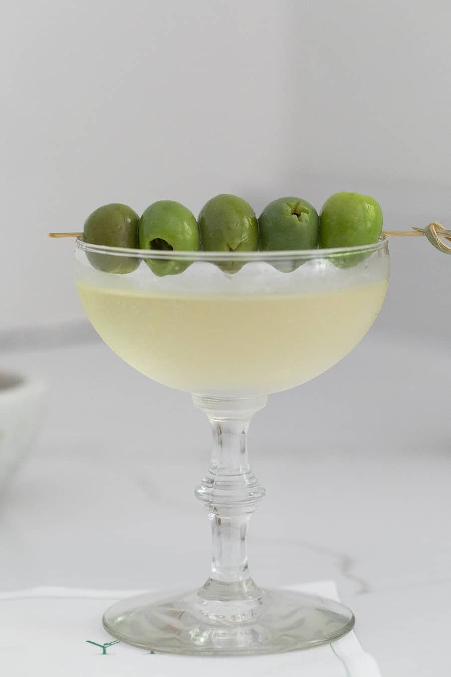 Green olives on a cocktail coupe