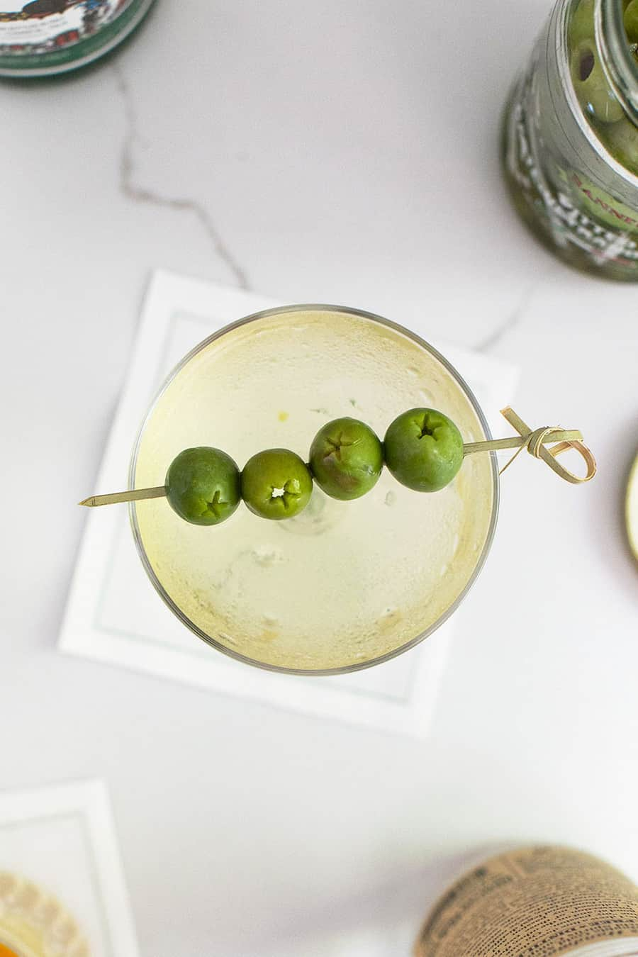 Dirty martini recipe in a coupe with 4 olives