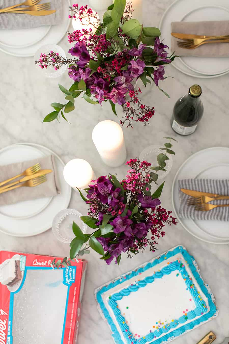 cake, flowers, sparkling apple cider and candles on a table for a back to school dinner.