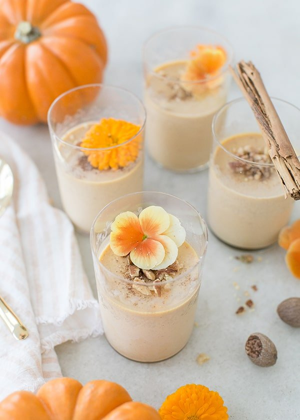 Pumpkin panna cotta halloween dessert with flowers and walnuts.