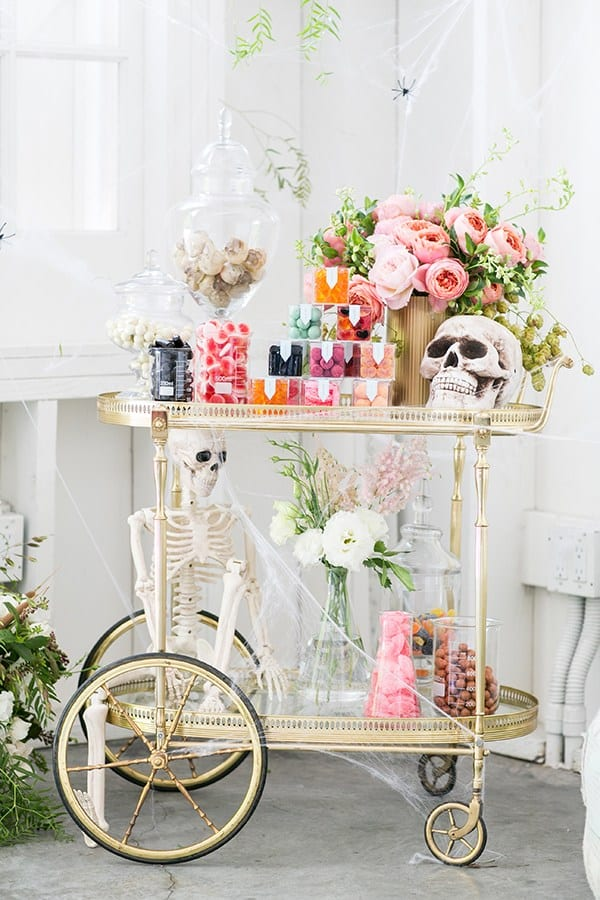 Halloween candy cart, candy, pink flowers, skeletons.