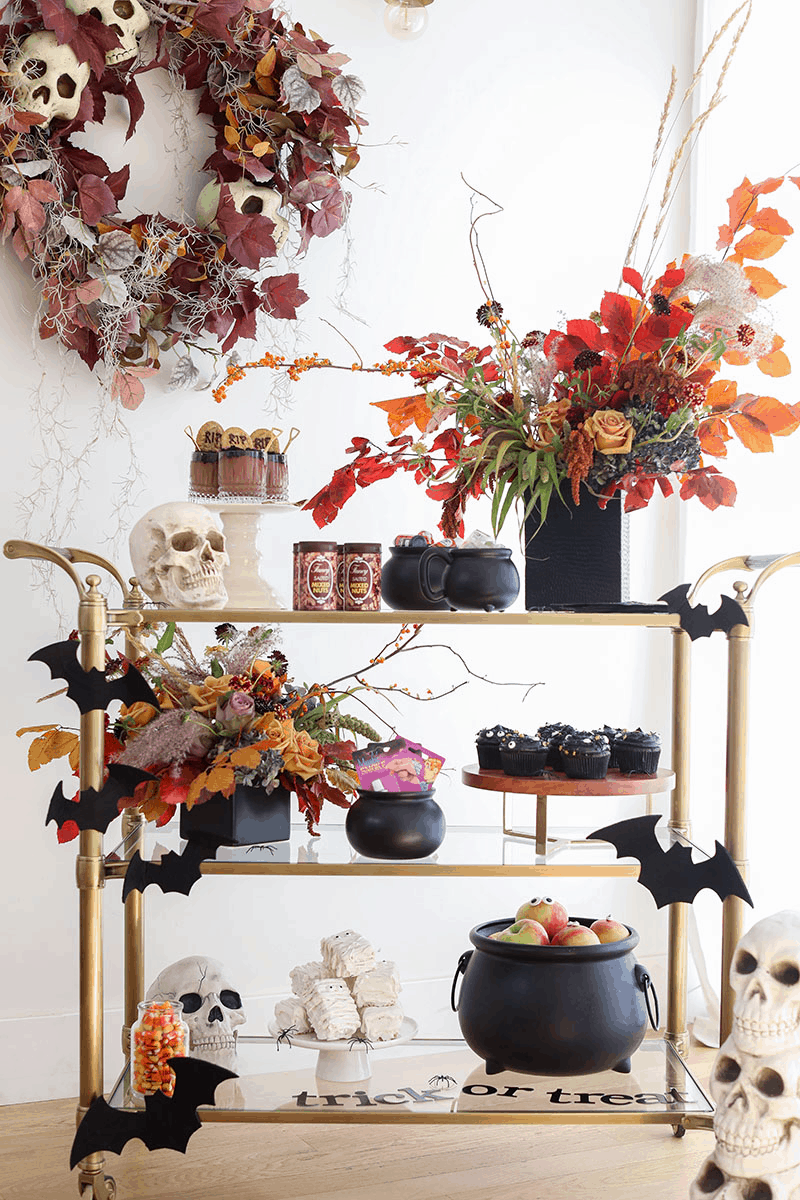 Halloween bar cart with cauldrons, flowers, skulls and desserts.