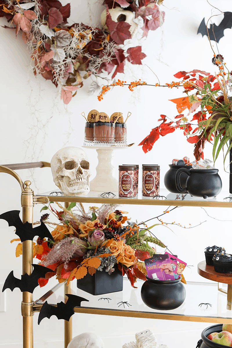 Halloween trick or treat bar setup with orange and yellow flowers, black cauldrons, dirt cup.
