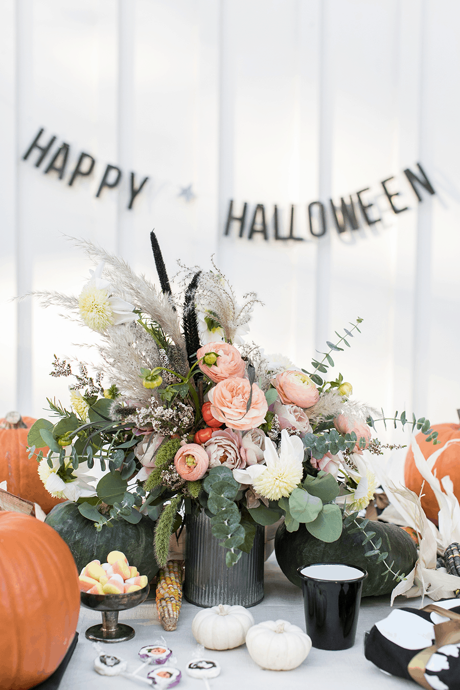 Happy Halloween sign and a galvanized vase full of flowers.