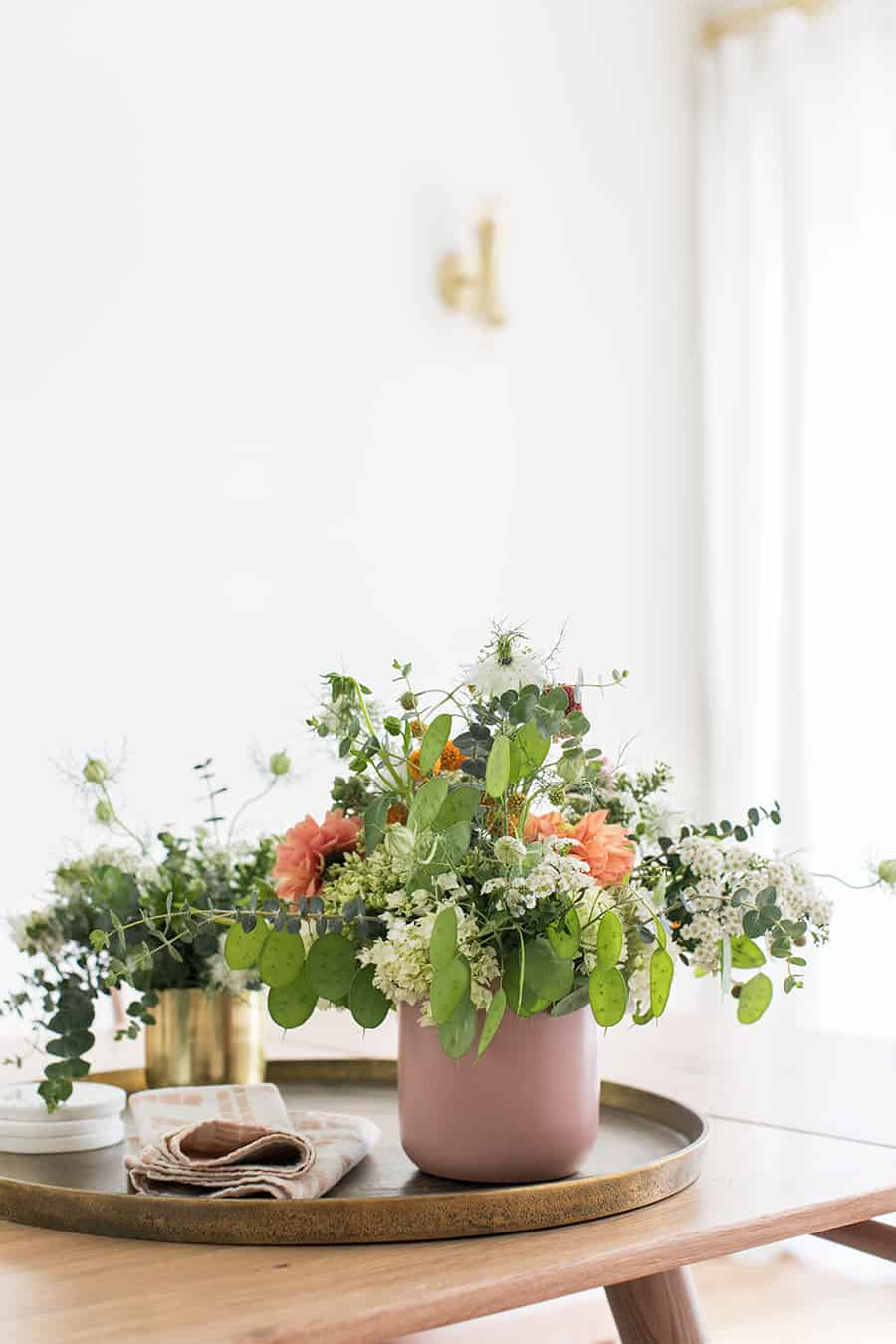 Fresh flowers in a pink vase on a wooden table to create a hygge lifestyle.