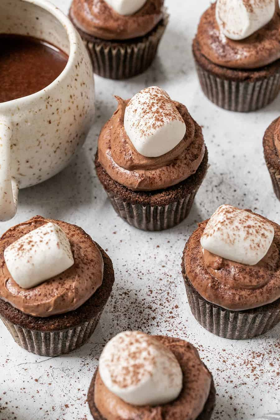 Hot Chocolate Cupcakes topped with marshmallows and sprinkled with hot chocolate.