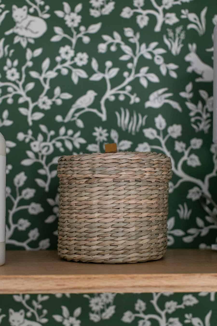 Woven basket on an oak shelf with green wallpaper.