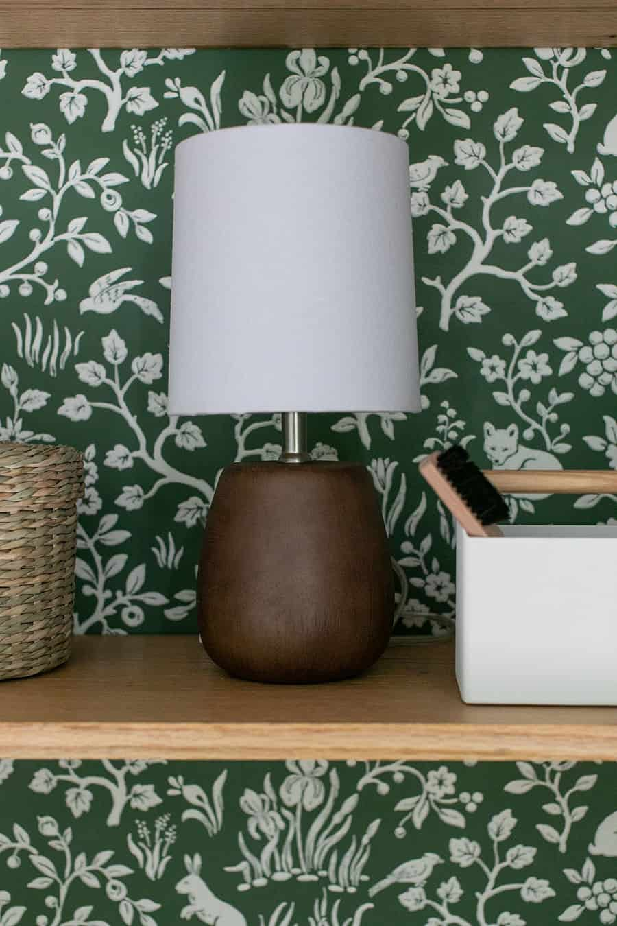 Wooden lamp on an oak shelf with green wallpaper.