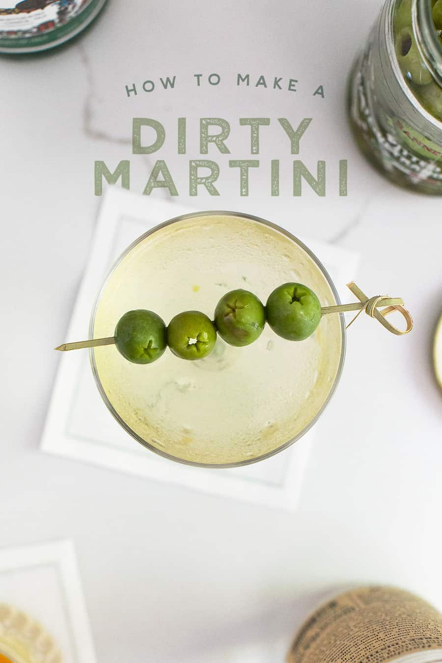 Dirty martini in a coupe with olives and a pick