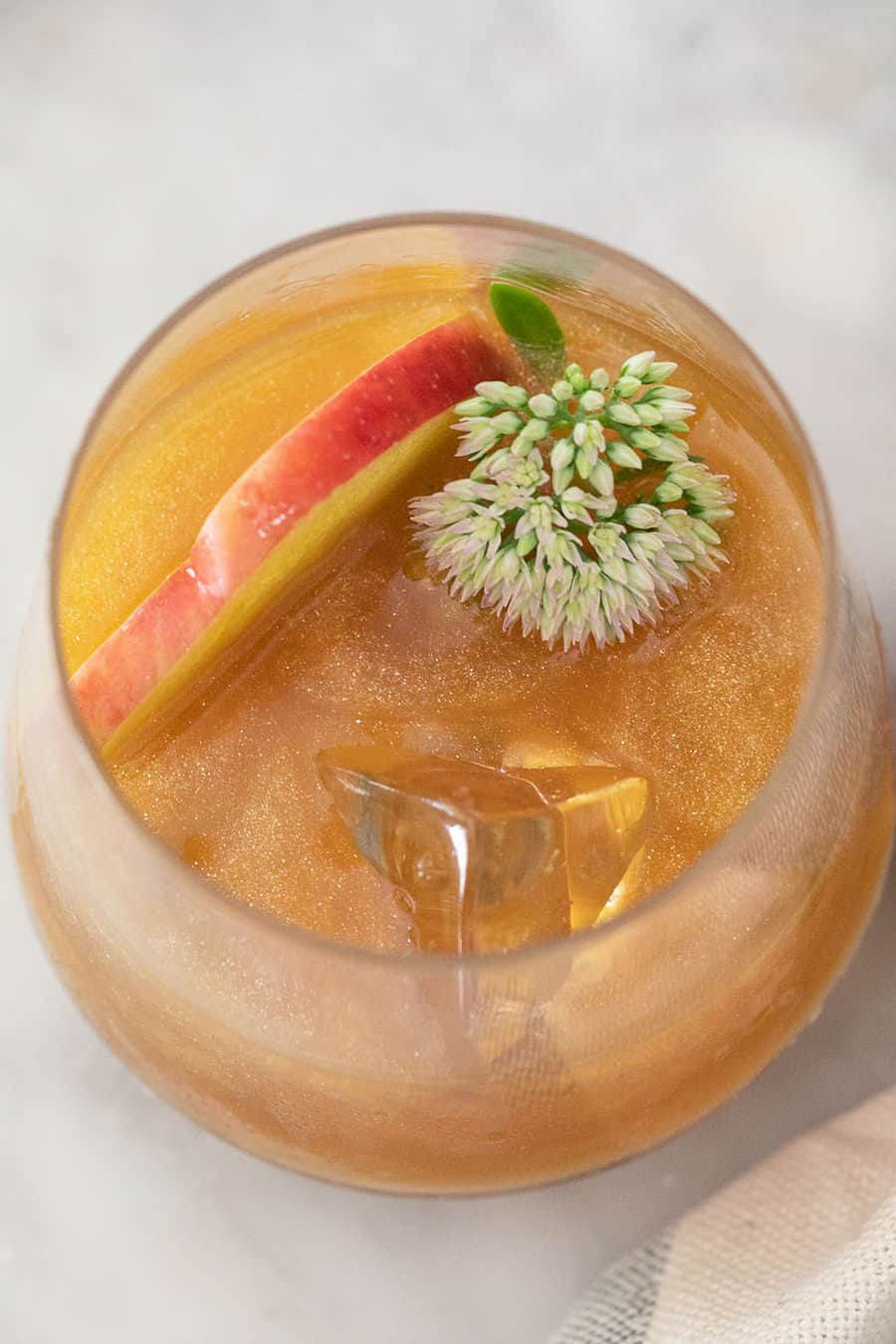 A poison apple cocktail with shimmer, flowers and apple slices.