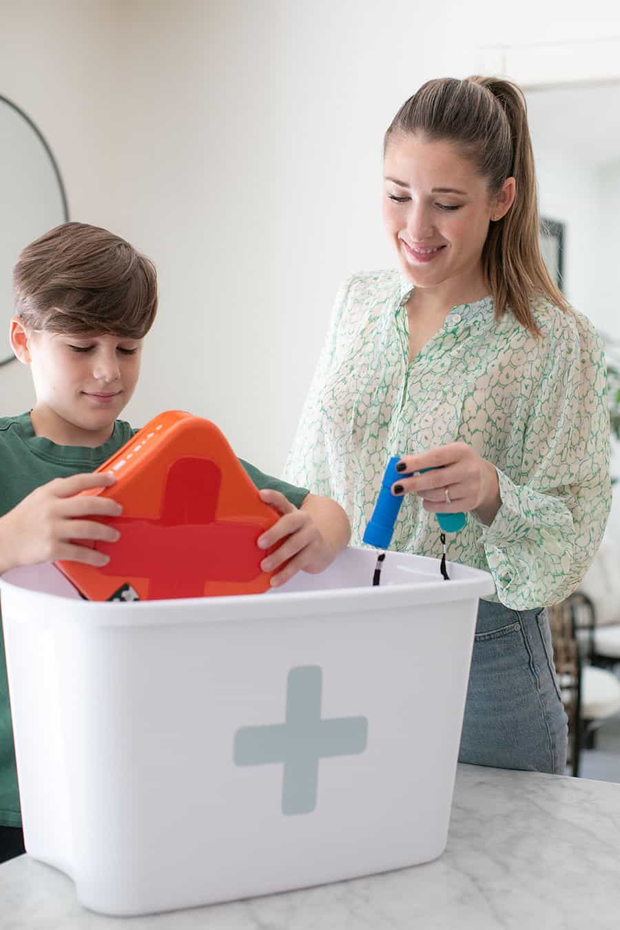 Eden Passante and son adding items into a bin to create a family emergency kit.