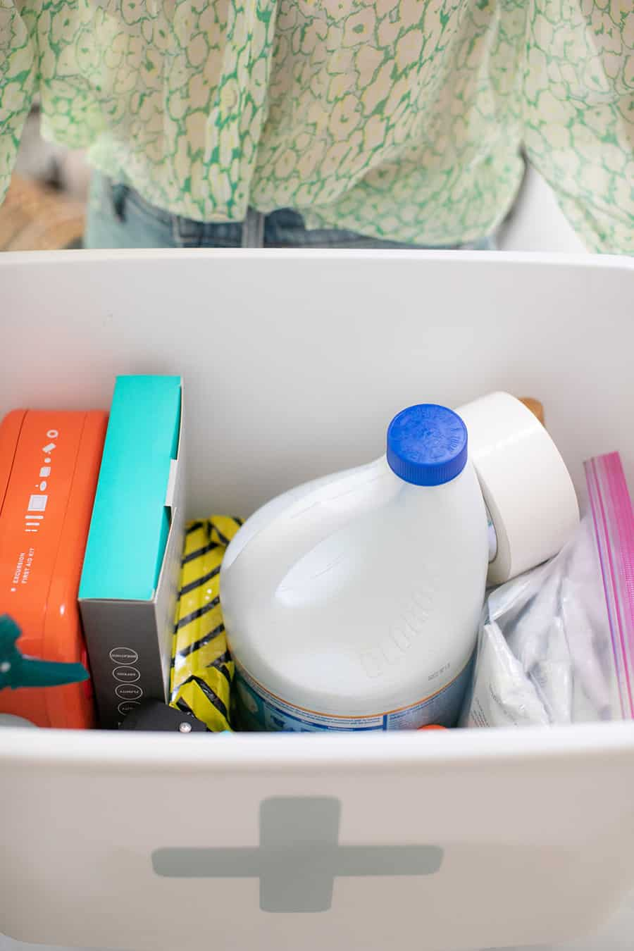 Emergency kit bucket with bleach, tape, masks, first aid kit and more items.