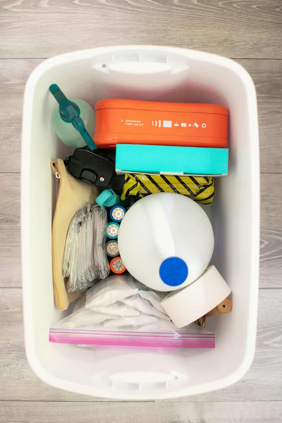 Emergency kit bucket filled with bleach, spray bottle, flashlights and more items.