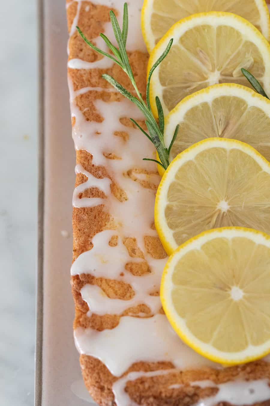 The top of a lemon loaf cake with sliced lemons and fresh rosemary,