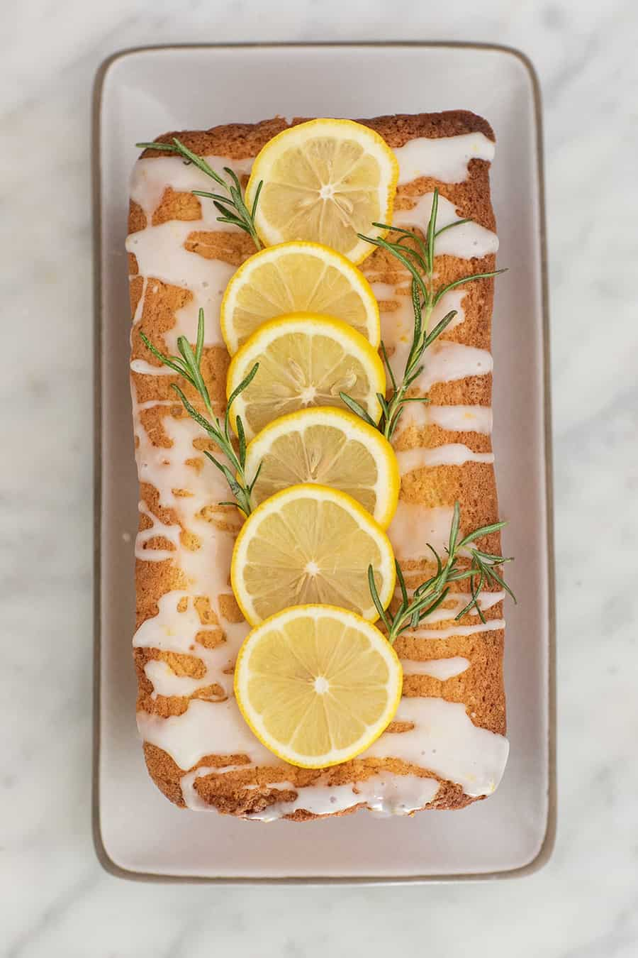 Lemon loaf cake with lemon slices and rosemary.
