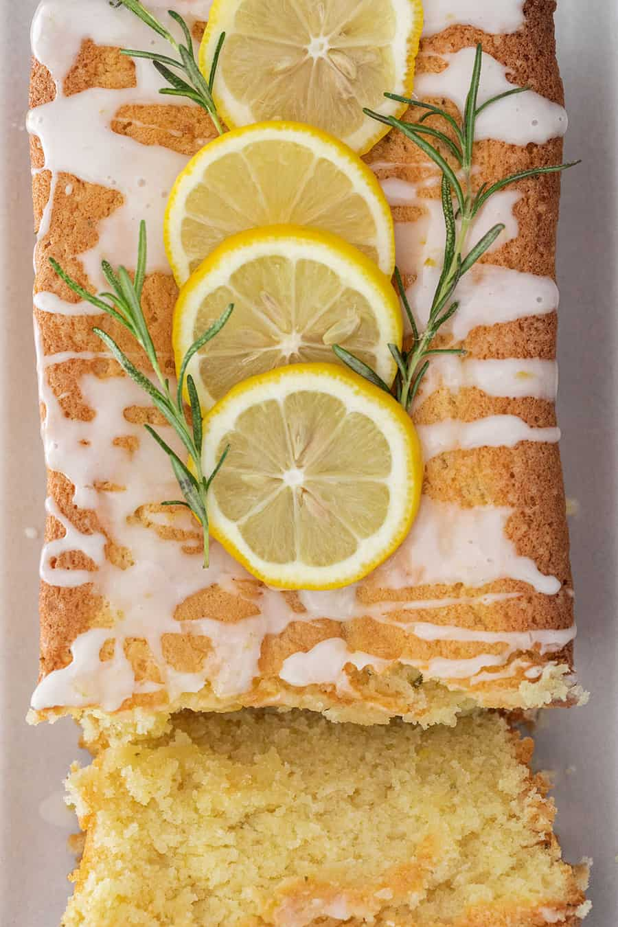 Rosemary Lemon Loaf cake cut with sliced lemon and fresh rosemary.