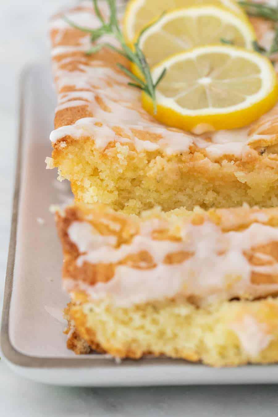 Buttery, moist lemon loaf cake cut with glaze poured over the top.