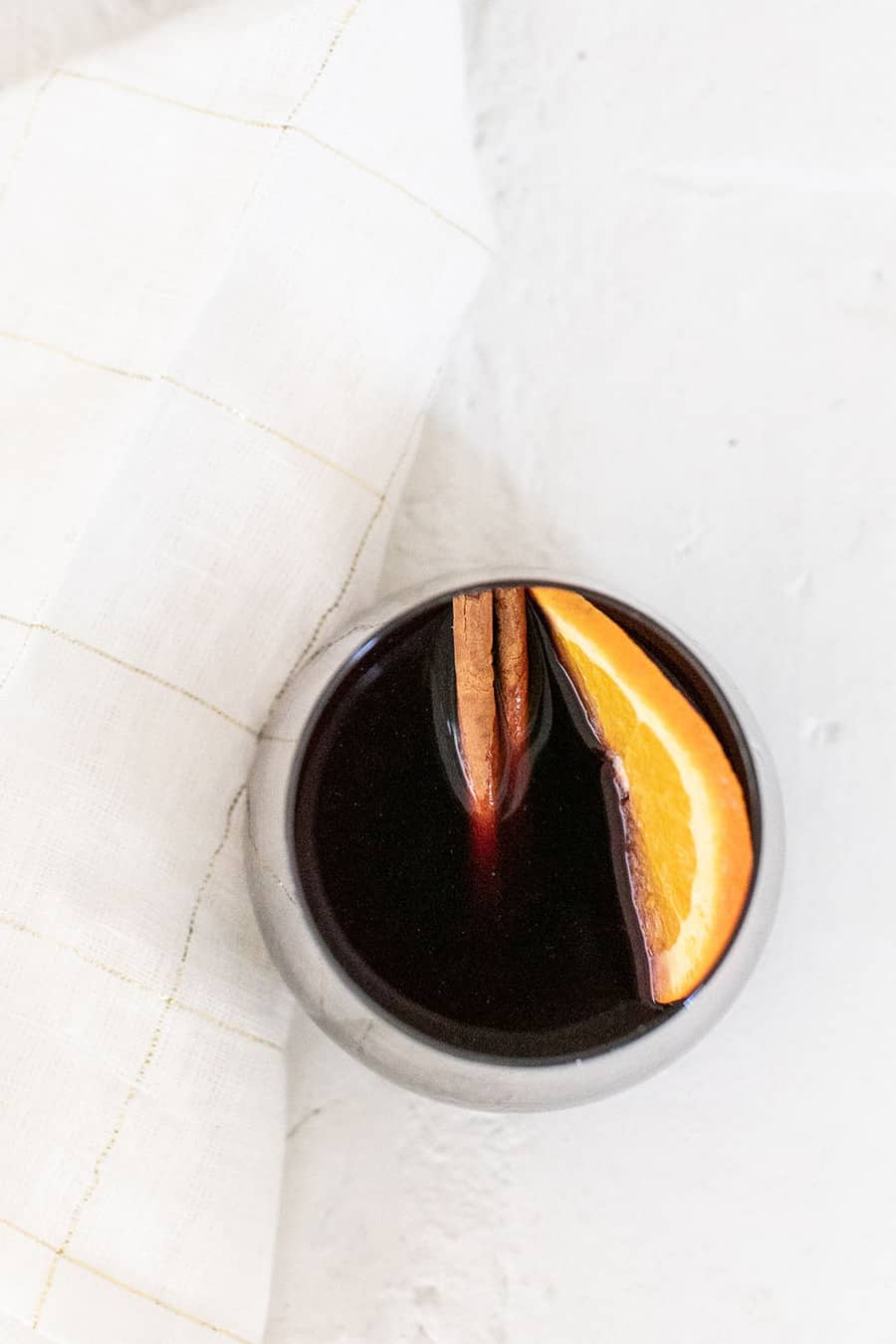Mulled wine with cinnamon stick and orange slice.