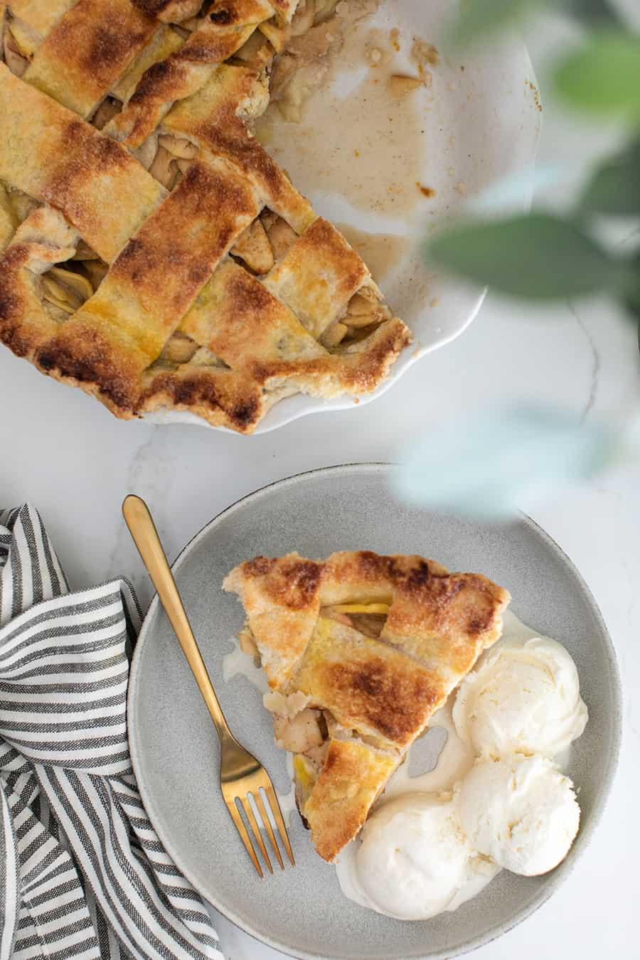 Slice of homemade apple pie with vanilla ice cream.