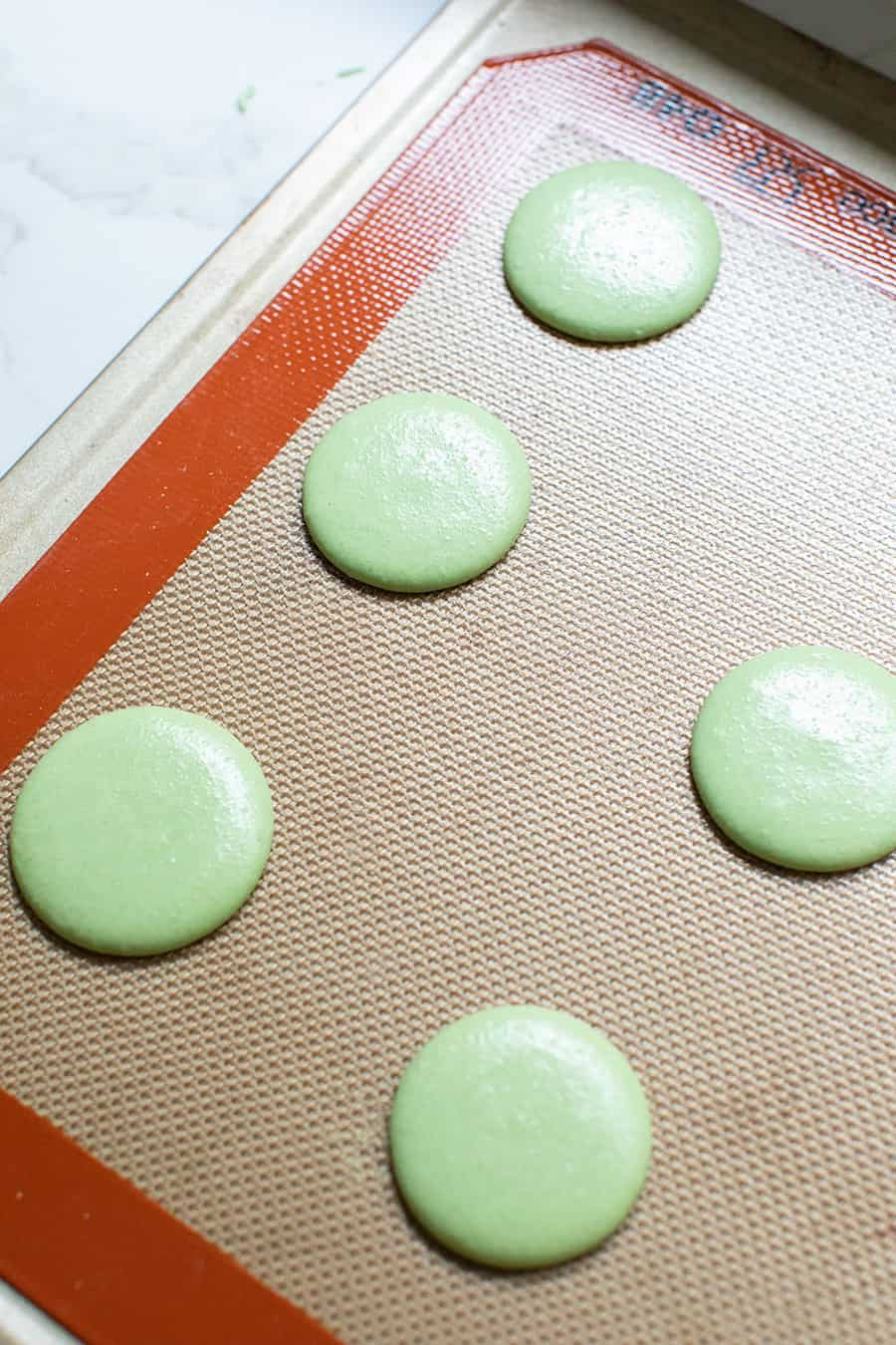 Green macaron cookies on a Silpat