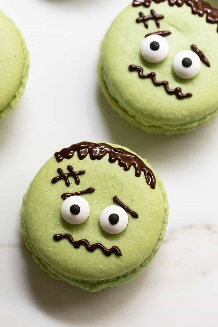 Green Frankenstein Macarons with eyes and chocolate face design.
