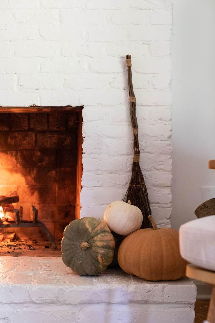 Pumpkins, broomsticks nd a fireplace.