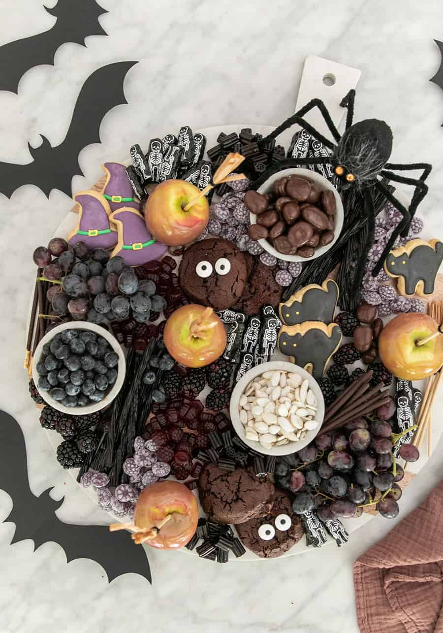 Halloween dessert platter filled with berries, chocolate, caramel apples, grapes and cookies.