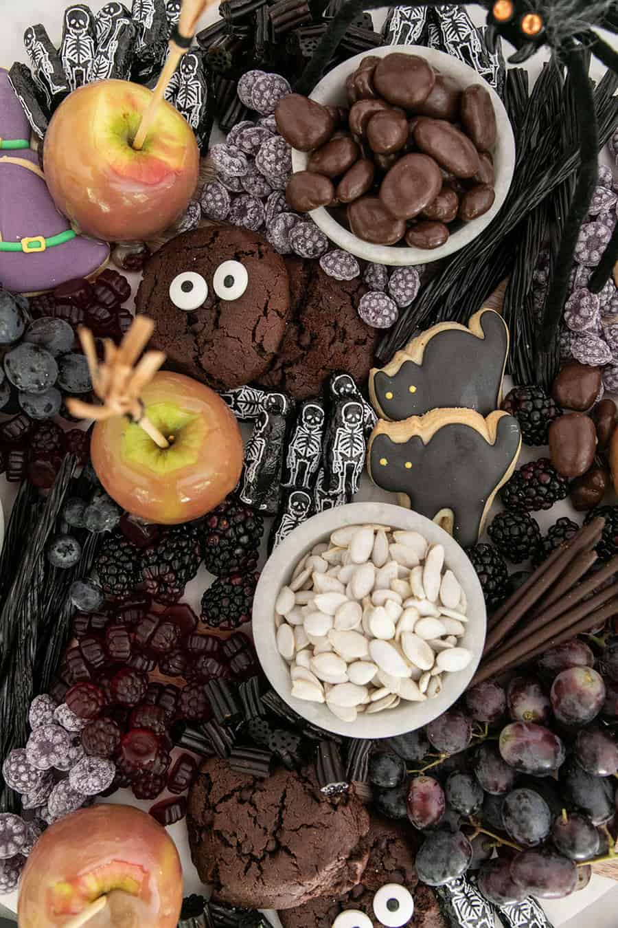 A Halloween dessert platter filled with caramel apples, fruit, chocolates and cookies.