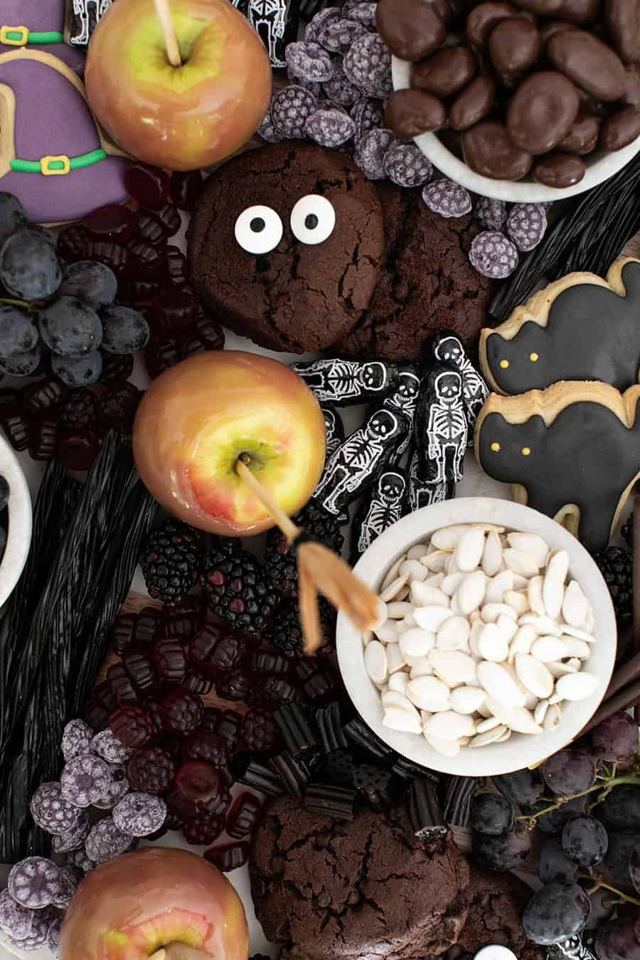 Halloween desserts on a platter. Cat cookies, chocolate cookies, sprinkles, chocolates