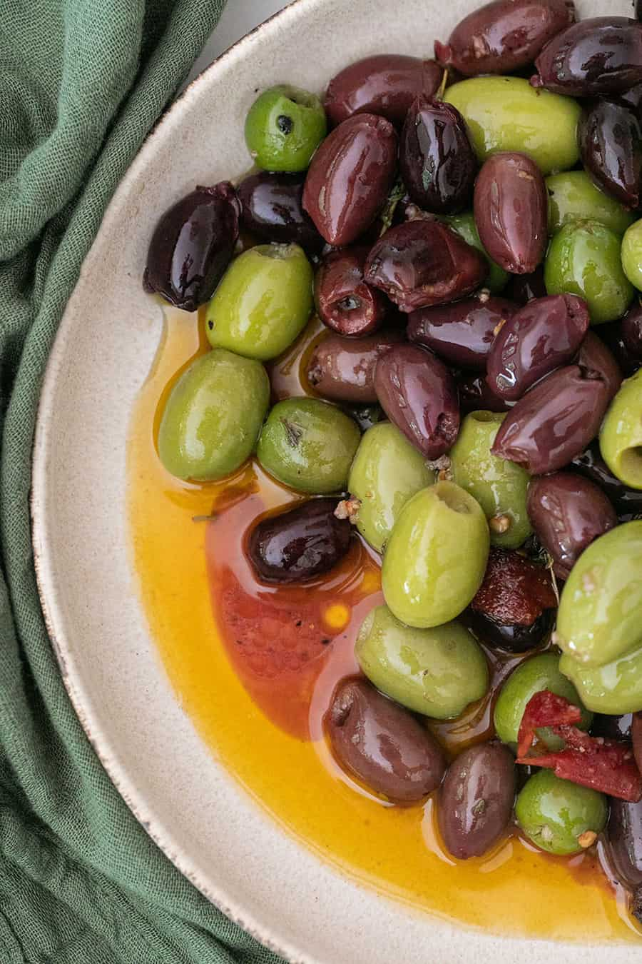 marinated green and kalamata olives in a bowl with sauce.