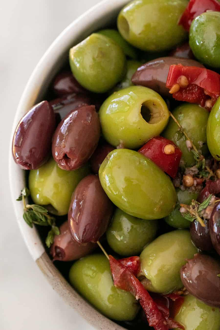 Close up of marinated olives with peppers and thyme.