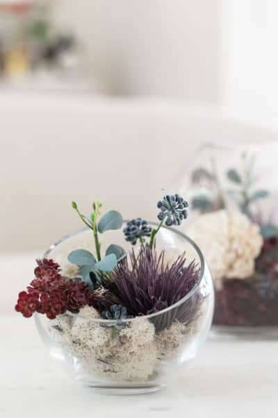 glass terrarium with flowers and moss