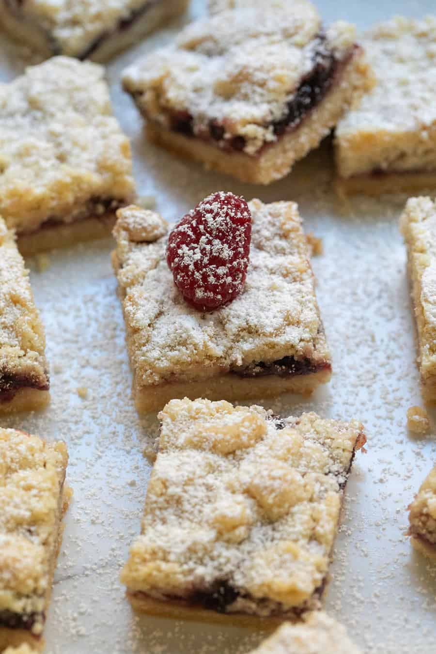 Crumble bars with powdered sugar and filled with raspberry.