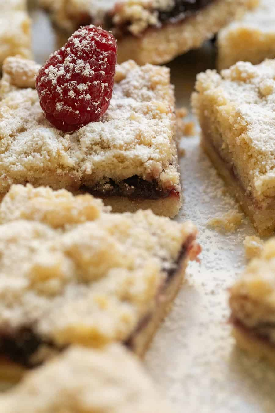Shortbread crumble bars with powdered sugar and a large raspberry on top.