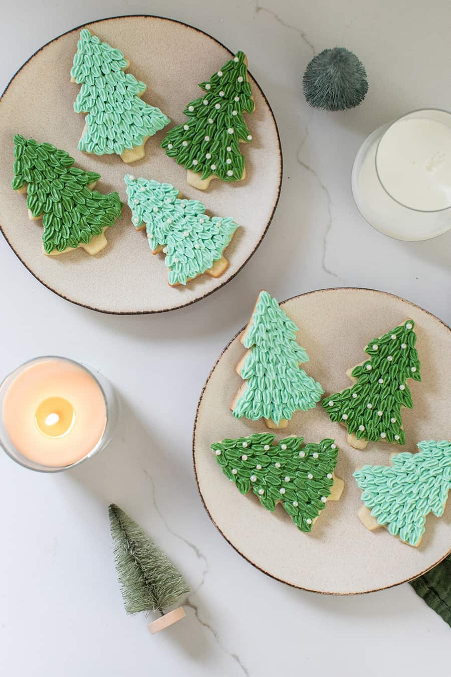 Christmas cookies on plates with a glass of milk.