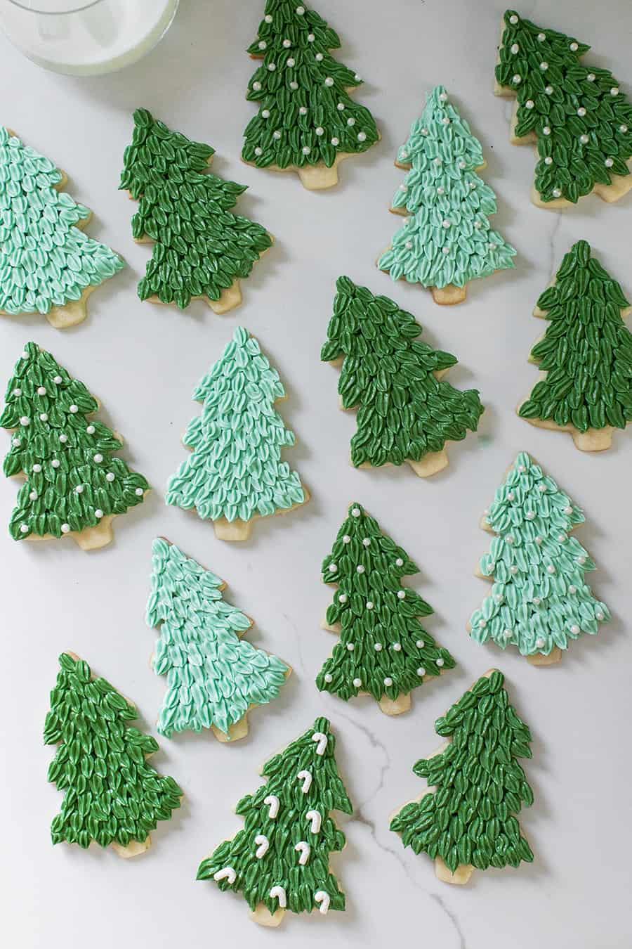Christmas tree sugar cookies on a  marble table.
