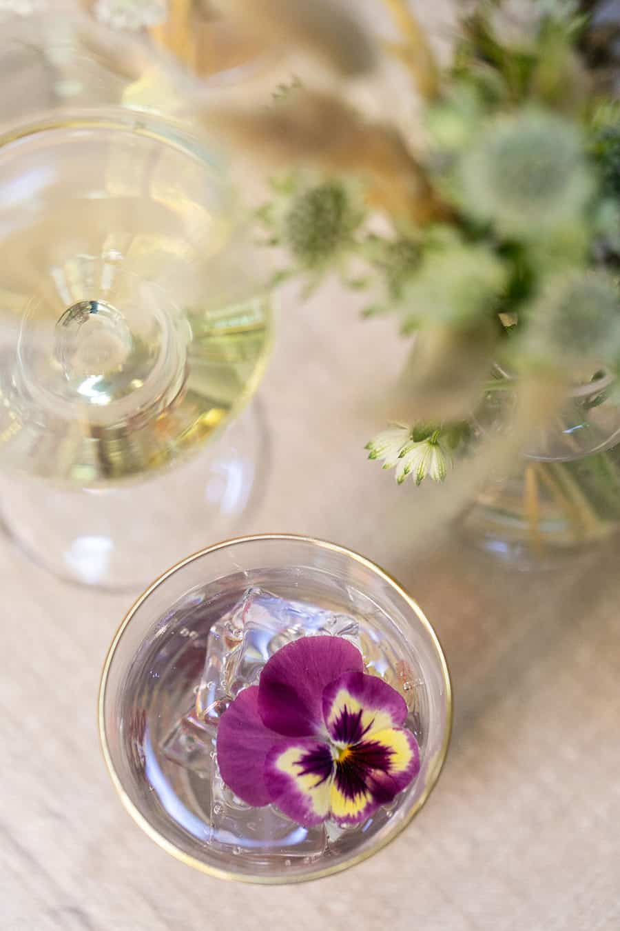 Water glass with a purple pansies