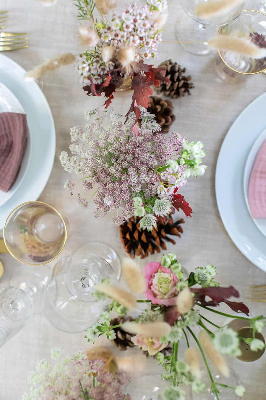 Thanksgiving table setting with flowers and pinecones