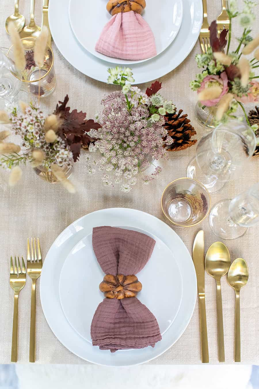 Simple fall Thanksgiving table setting, white plates, gold flatware and pretty flowers.