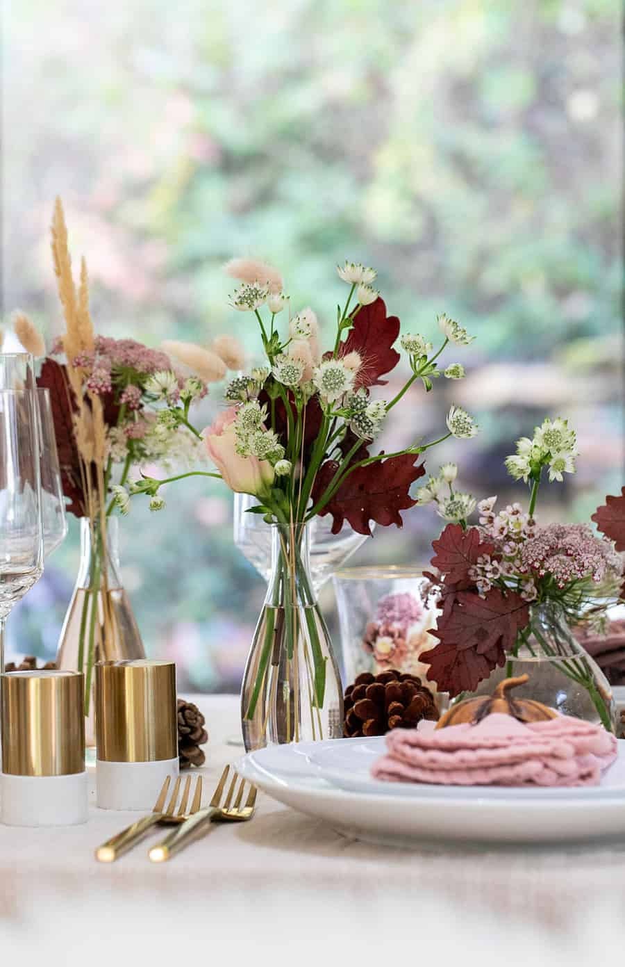 Bud vases with flowers, salt and pepper shaker and gold flatware.