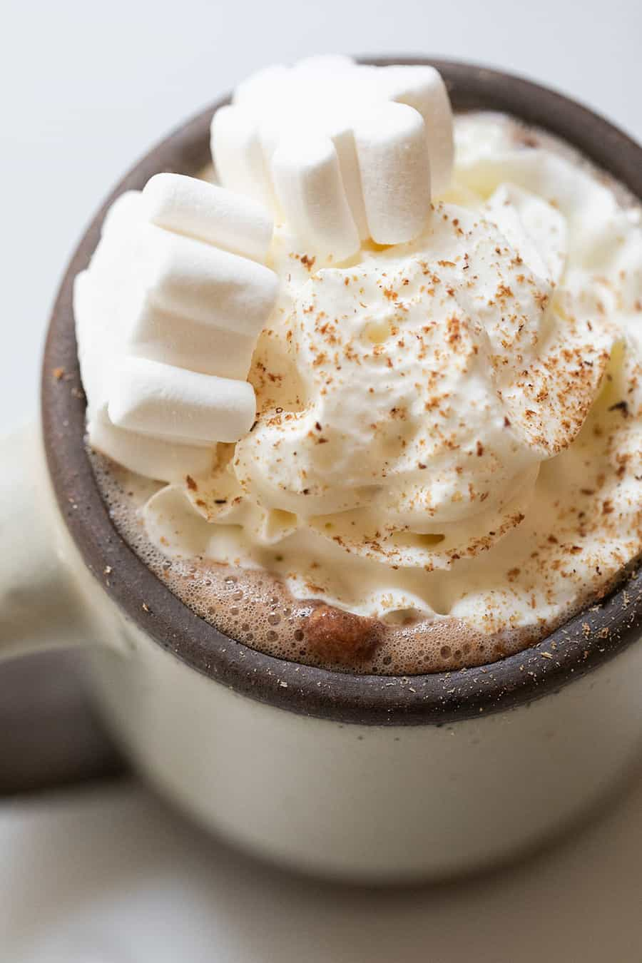 Hot chocolate topped with whipped cream, nutmeg and marshmallows.