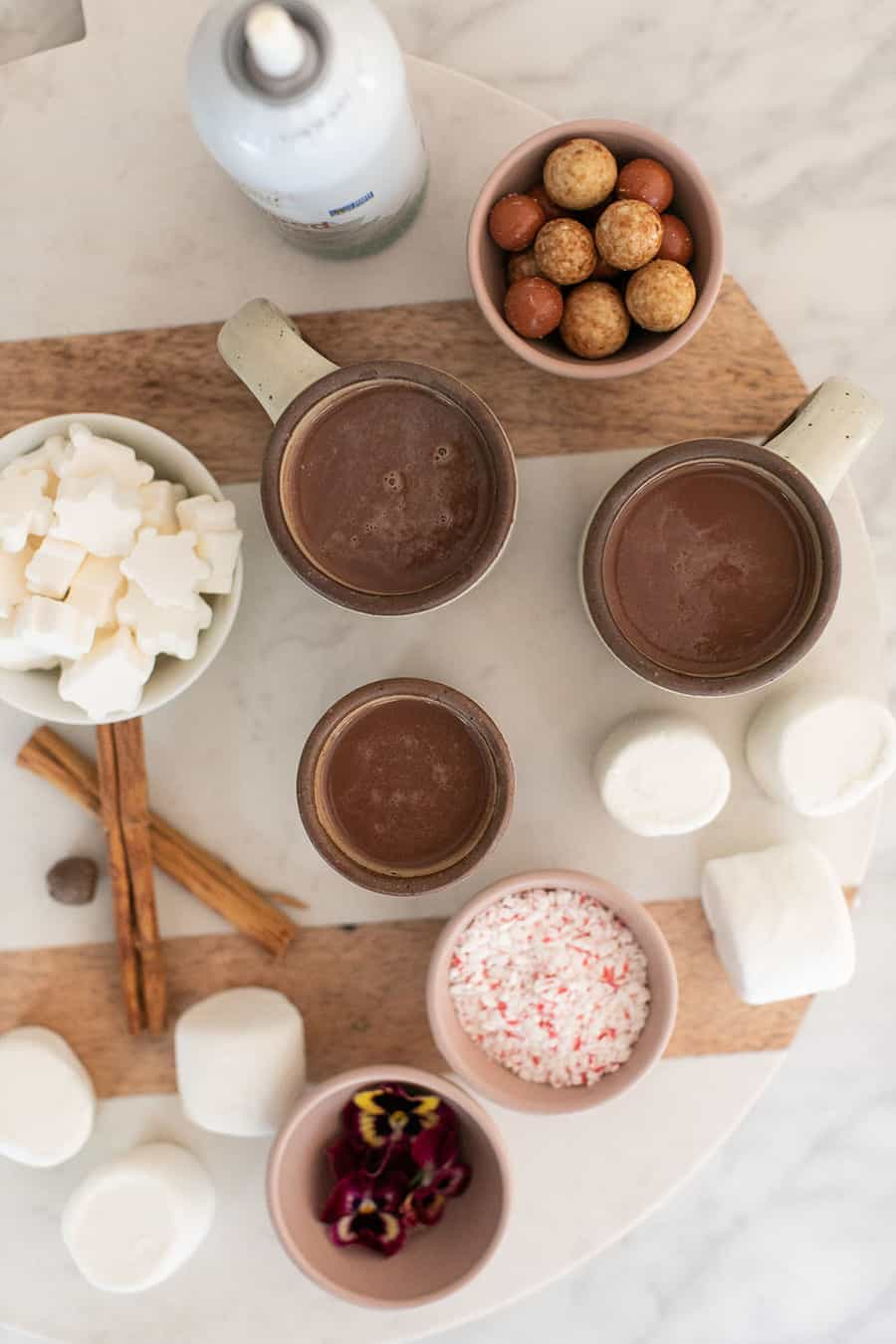 Hot chocolate on a board with mugs filled with hot chocolate