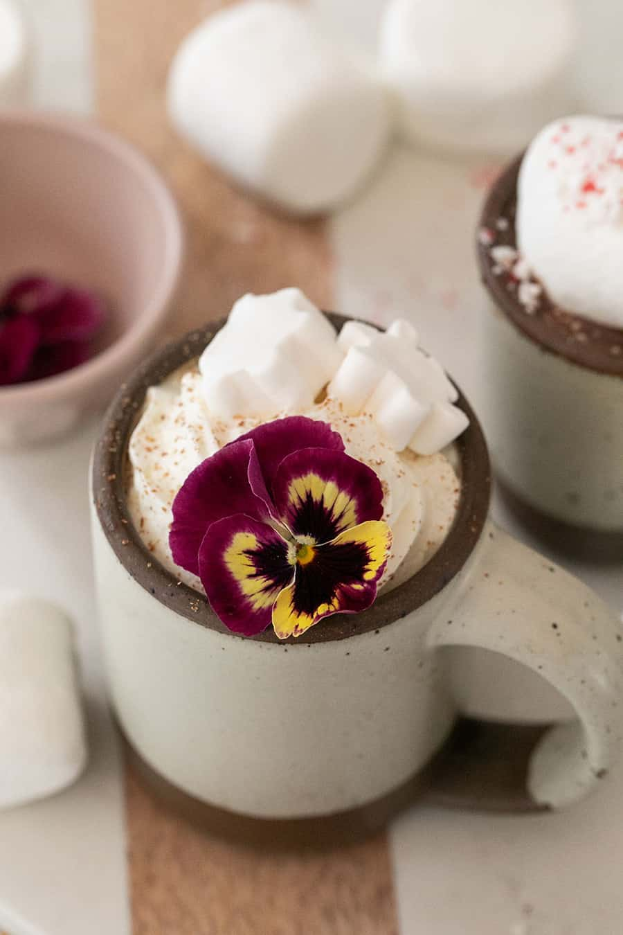 Hot chocolate in a mug topped with whipped cream and an edible flower.
