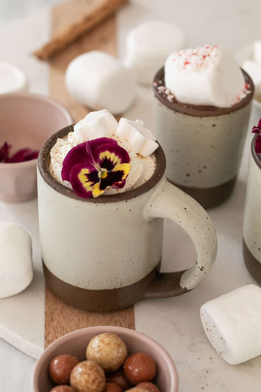 Mug filled with hot chocolate topped with whipped cream, a marshmallow and an edible flower.