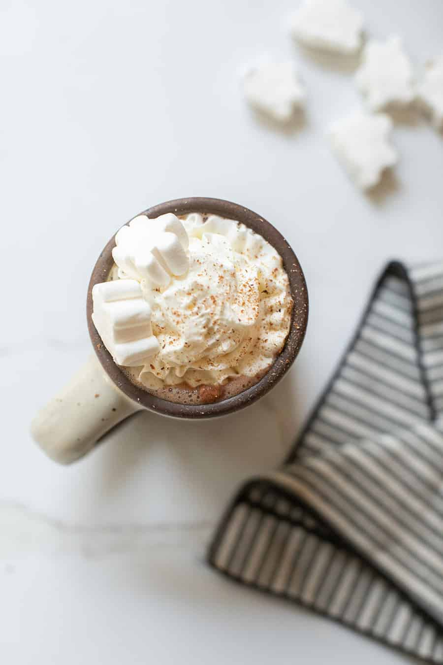 Hot chocolate recipe in a mug with whipped cream and marshmallows.