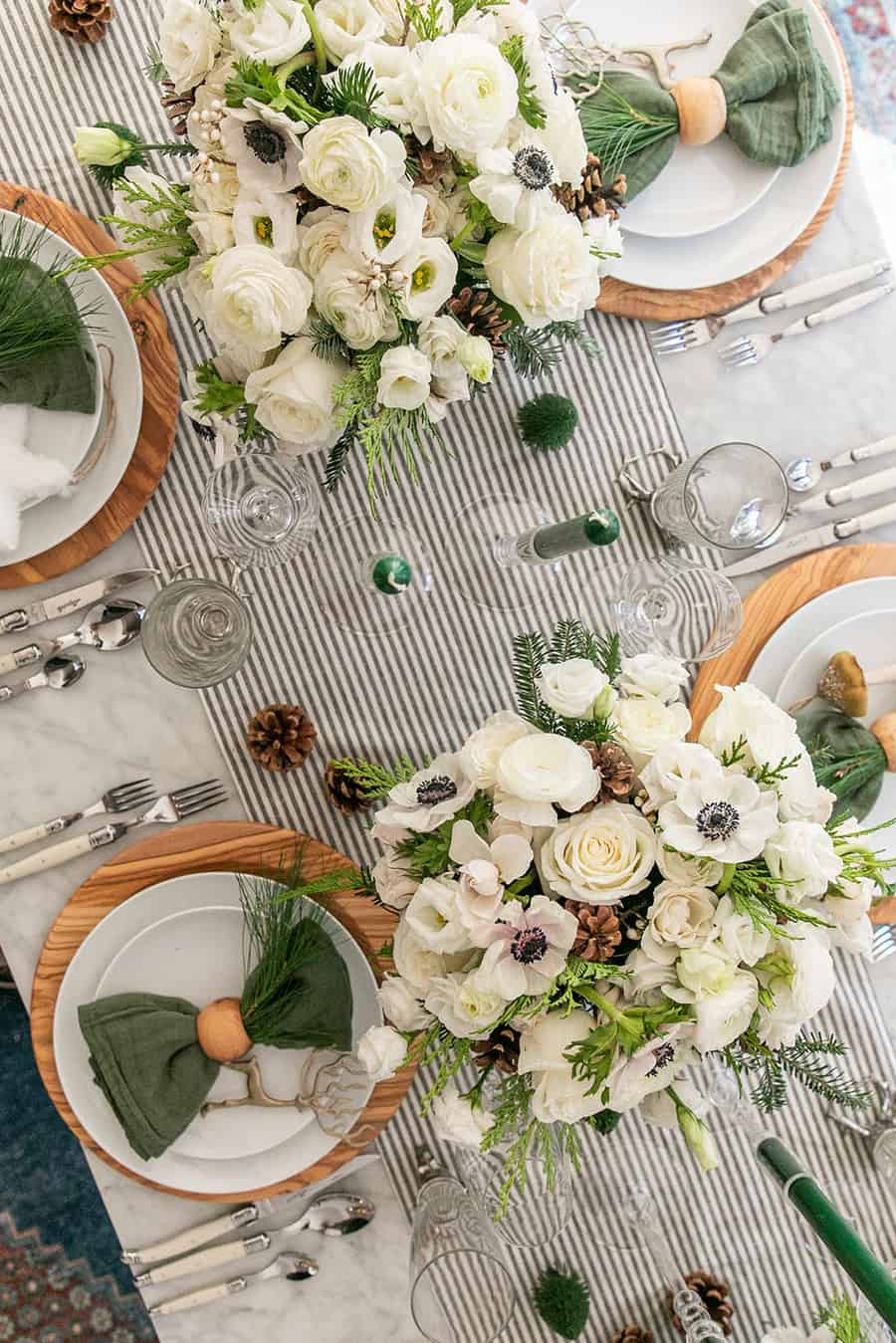 Flowers on a table with a striped table runner.