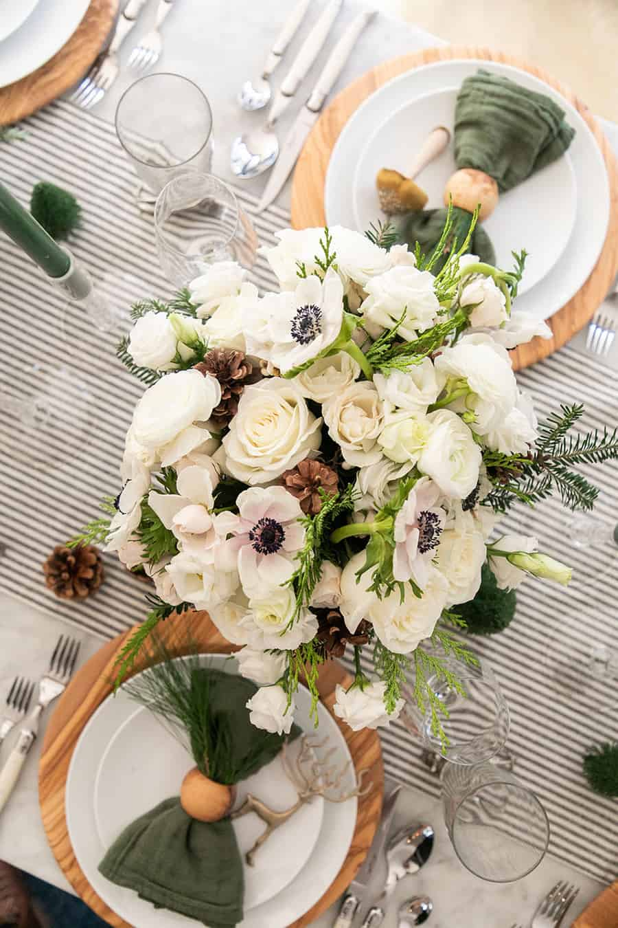 Christmas flower arrangement on a table with striped linen table runner.